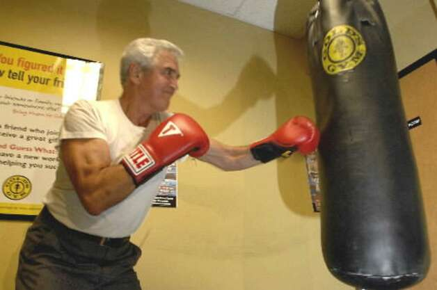 Senate Majority Leader Joseph Bruno hits the bag during an appearance with Troy heavyweight boxer Shannon Miller on Oct. 10, 2007, at Gold's Gym in Latham. (Times Union file photo)