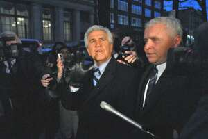 Former State Senate Majority Leader Joseph Bruno was found guilty on two of eight federal counts against him. He waves to a  woman who shouted words of encouragement to him as he is escorted away from the federal courthouse following his Dec. 7, 2009, conviction for corruption.  His spokesman,  Kris Thompson, is at far right, as they walk on Broadway away from the courthouse.  (Philip Kamrass /  Times Union)