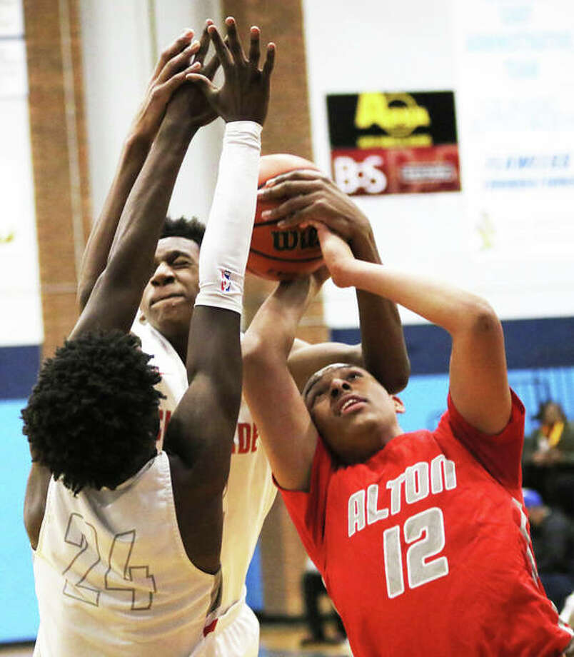 Alton's Josh Rivers (12) is fouled while going up for a shot over Chaminade's Harrison Vickers (24) and Tarris Reed Jr. (back) on Saturday night in the Belleville East Tournament championship game in Belleville. Photo: Greg Shashack / The Telegraph
