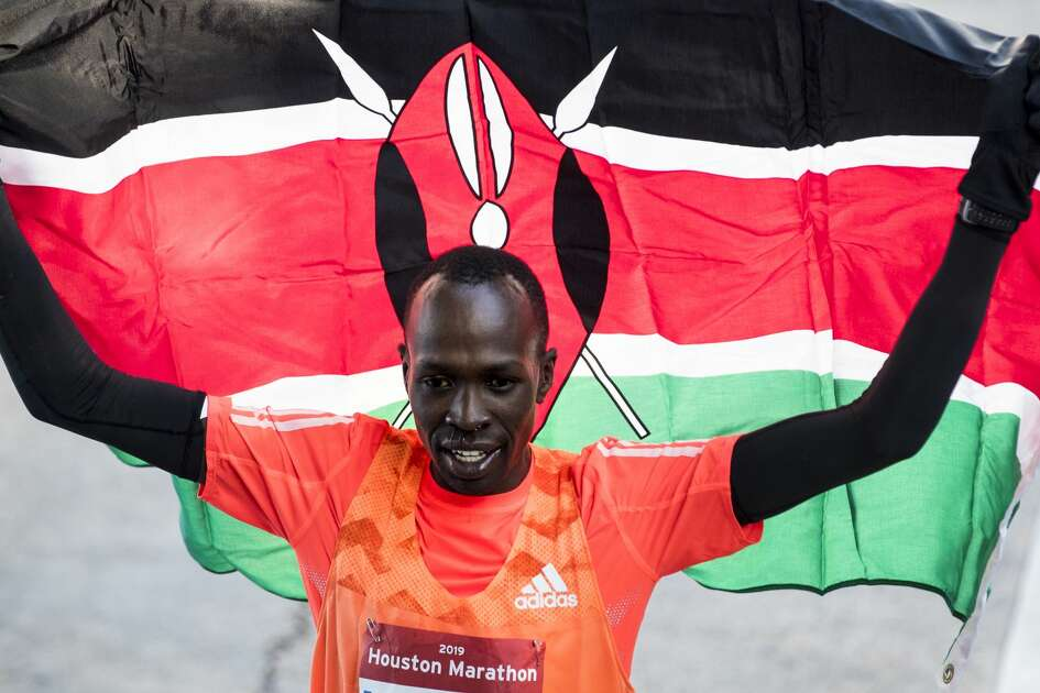 Albert Korir, of Kenya, hoists his country's flag as he celebrates his win in the Chevron Houston Marathon with a time of 2:10:02 on Sunday, Jan. 20, 2019, in Houston.