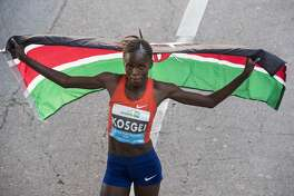 Brigid Kosgei, of Kenya, hoists her country's flag after winning the women's race of the Aramco Half Marathon with a time of 1:05:50 on Sunday, Jan. 20, 2019, in Houston.