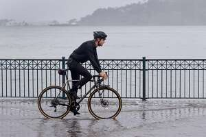 Froste Wistrom rides his bike through rising bay water during the peak of high tide along the Embarcadero in San Francisco, Calif. on Tuesday, Nov. 24, 2015. King tide conditions are causing higher than usual water levels.