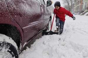 Sami Al-Tiri, 10, digs out the family car on Sunday, Jan. 20, 2019, in Albany, N.Y.   (Paul Buckowski/Times Union)