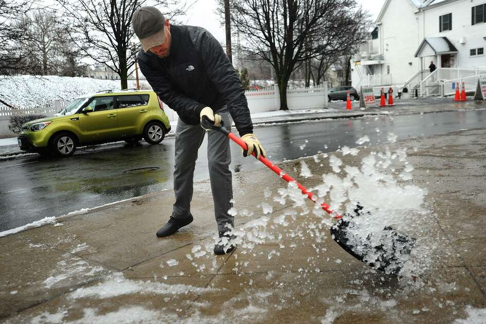 Mike Porcello, general manager of Eli's Tavern, clears slush from the sidewalks outside the restaurant on Daniel Street in Milford, Conn. on Sunday, January 20, 2019.
