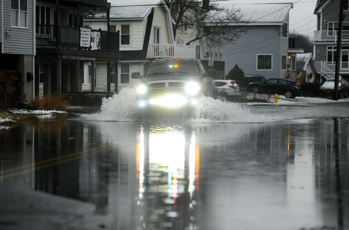 A pickup truck makes its way down Bayshore Drive, flooded during a high storm tide, in Milford, Conn. on Sunday, January 20, 2019.
