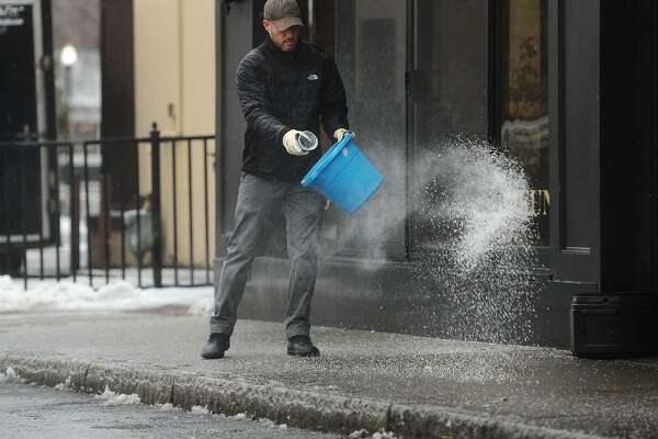Mike Porcello, general manager of Eli's Tavern, spreads salt on the sidewalks outside the restaurant on Daniel Street in Milford, Conn. on Sunday, January 20, 2019.