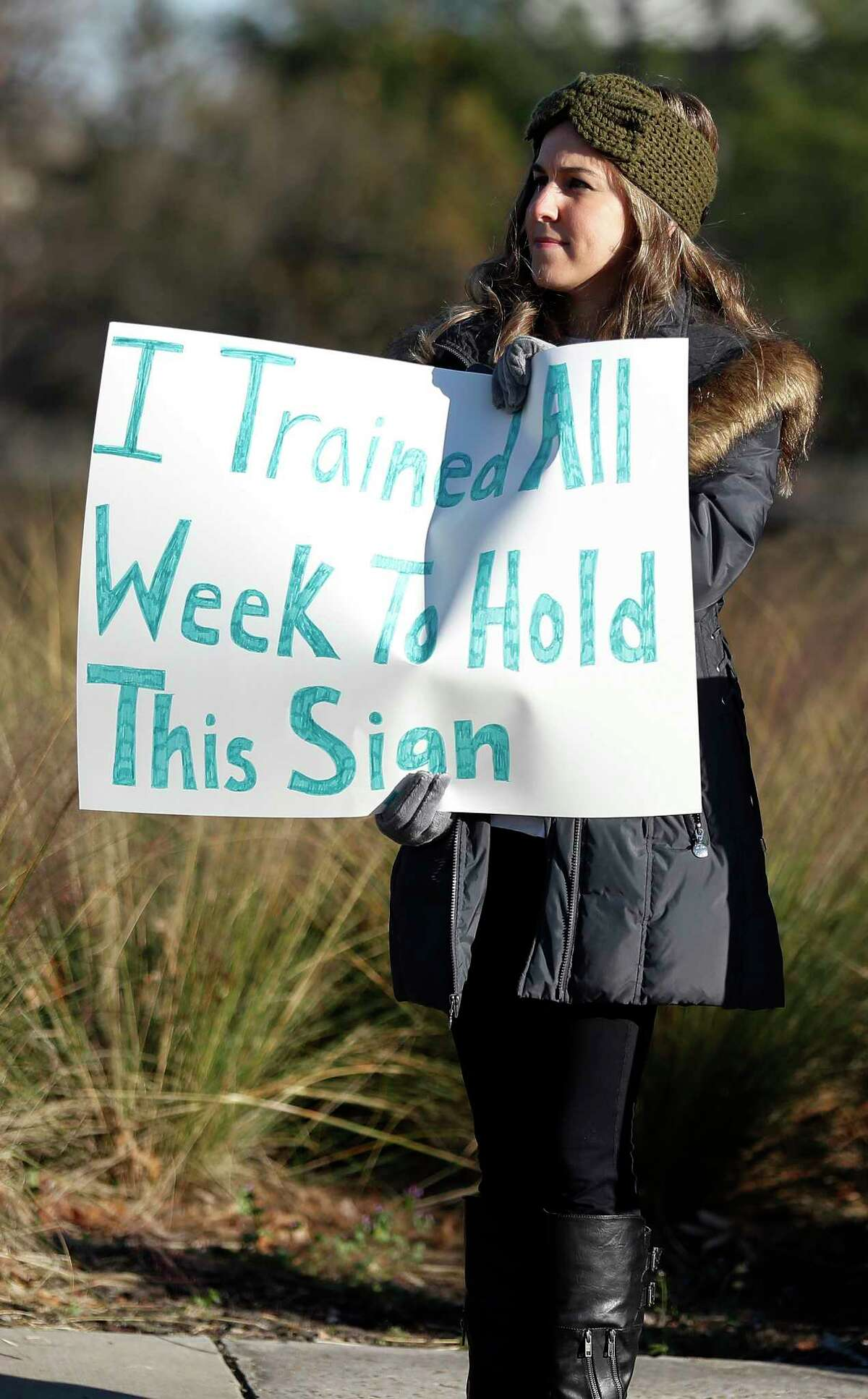 A Half-marathon supporter holds a sign to cheer on runners near mile marker 11 at Montrose and Allen Parkway during the Chevron Houston Marathon, Sunday, Jan. 20, 2019, in Houston.