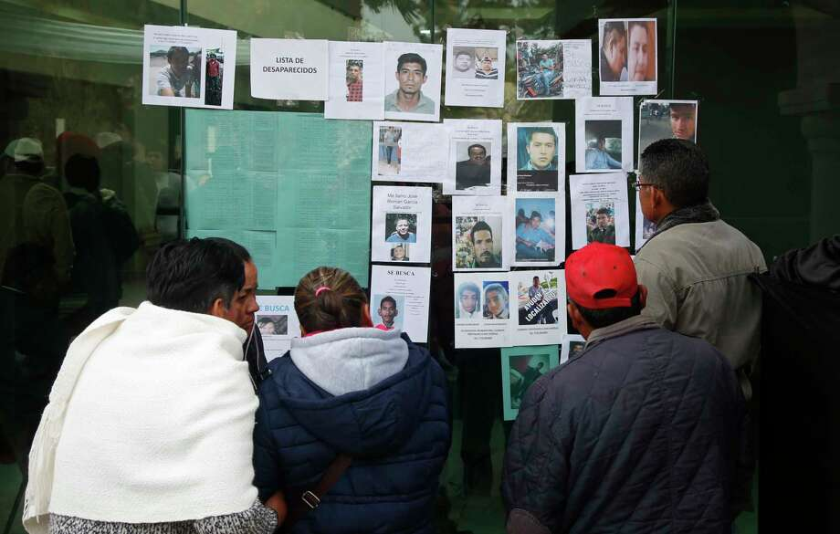 People look at photographs of people who are missing since the pipeline accident in Tlahuelilpan, Mexico, Sunday Jan. 20, 2019. A massive fireball that engulfed locals scooping up fuel spilling from a pipeline ruptured by thieves in central Mexico killed dozens of people and badly burned dozens more on Jan. 18. Photo: Claudio Cruz, AP / Copyright 2019 The Associated Press. All rights reserved.
