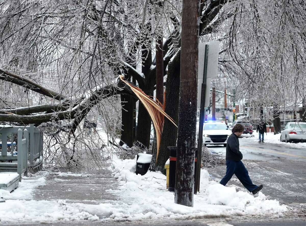 An ice covered tree limb blocks the sidewalk at the corner of Canner and Orange Street in New Haven on January 20, 2019.