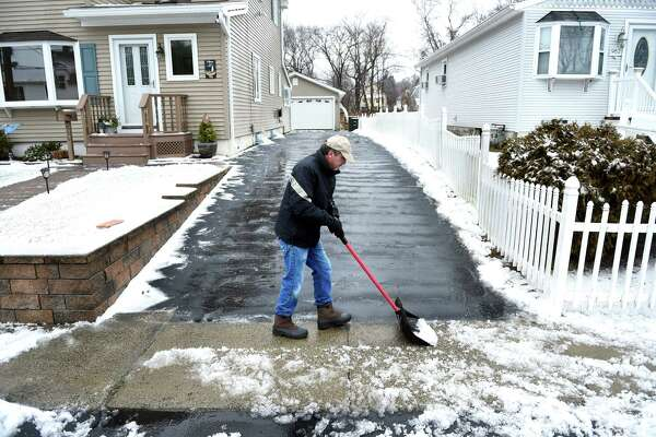 Dave Allen clears his driveway of snow and sleet in Milford on January 20, 2019.