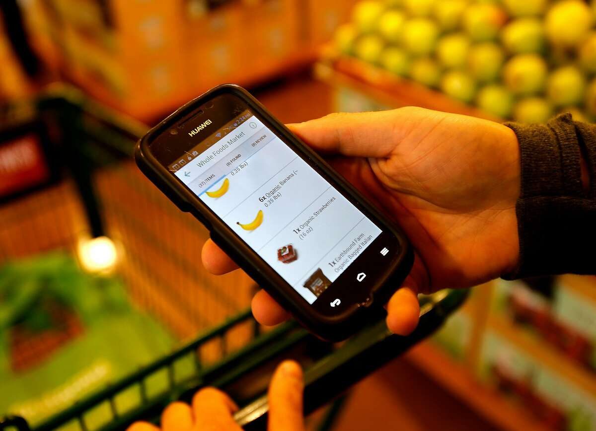 On Instacart, Yonatan Schkolnik uses his application to see the shopping he must do for the client Monday November 10, 2014 at a Whole Foods in Berkeley, Calif. Yonatan Schkolnik drives paying customers for Sidecar and delivers groceries for Instacart in the Bay Area.
