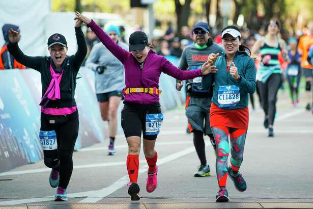 Loan Nguyen, left, Tho Nguyen and Kim Thoi Nguyen cross the finish line of the Chevron Houston Marathon together on Sunday, Jan. 20, 2019, in Houston.