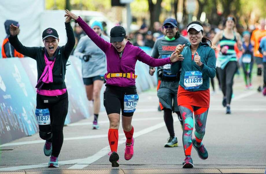 Loan Nguyen, from left, Tho Nguyen and Kim Thoi Nguyen cross the finish line of the Chevron Houston Marathon on Sunday. Photo: Brett Coomer, Houston Chronicle / Staff Photographer / © 2019 Houston Chronicle