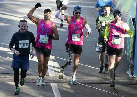 Mark Poole, far left, crosses the finish line of the Aramco Half Marathon with Mark Barr (41015) with his running guides on Sunday, Jan. 20, 2019, in Houston.