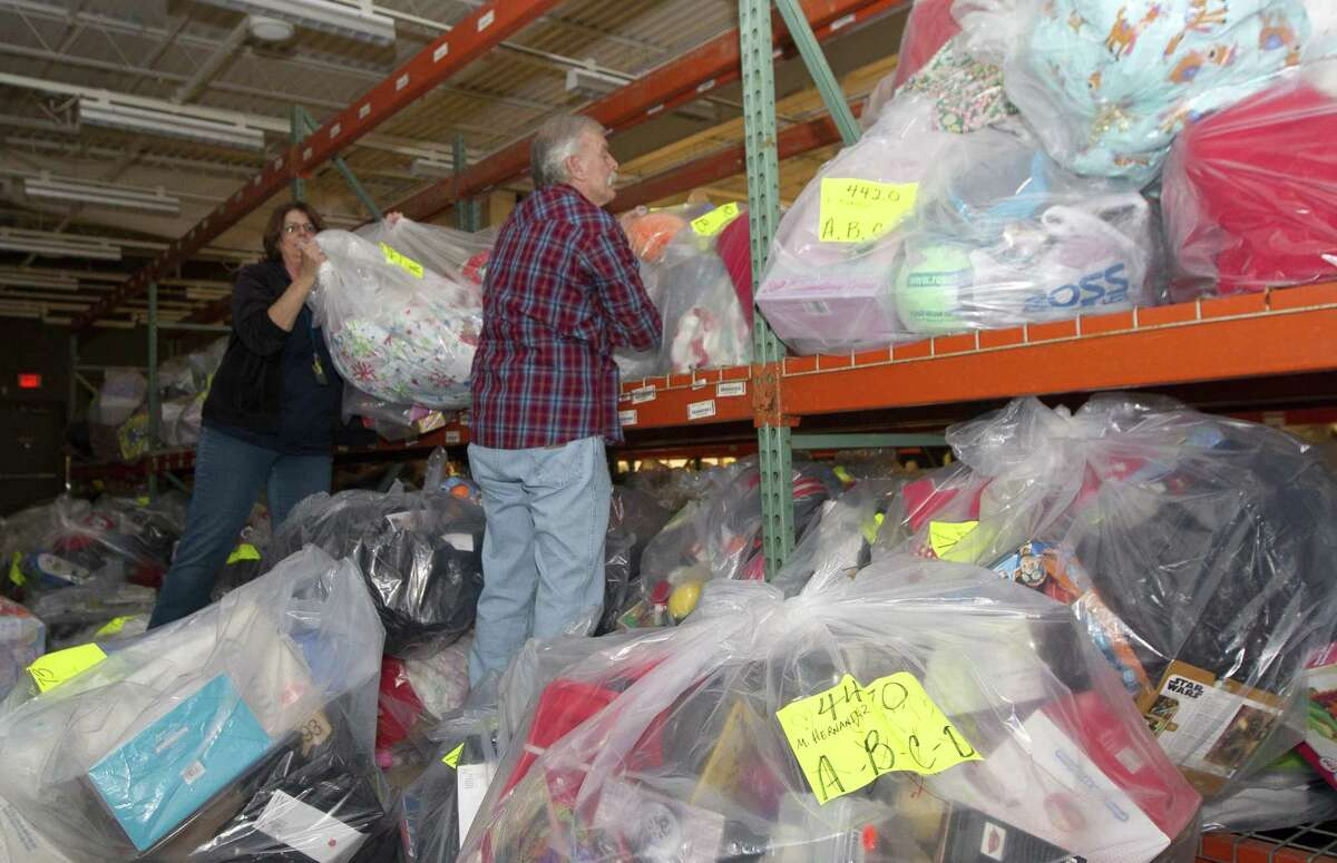 Volunteers check bags of gifts and clothes during the Salvation Army's annual angel tree gift assistance program at the Conroe Outlet Mall, Wednesday, Dec. 19, 2018, in Conroe. The event provided toys and clothes for 4,500 children and more than 500 senior citizens.