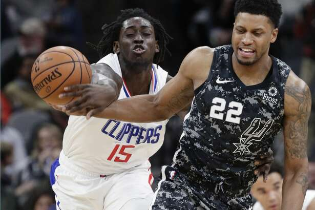 Los Angeles Clippers forward Johnathan Motley (15) steals the ball from San Antonio Spurs forward Rudy Gay (22) during the first half of an NBA basketball game, Sunday, Jan. 20, 2019, in San Antonio. (AP Photo/Eric Gay)