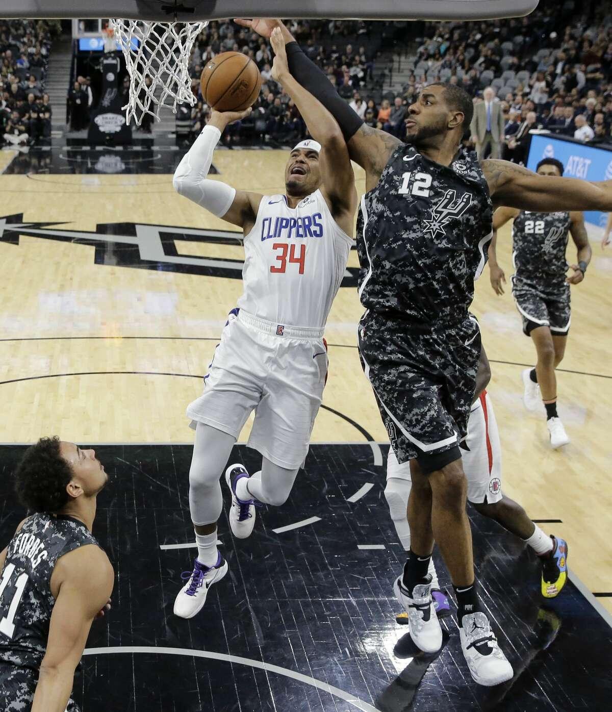 Los Angeles Clippers forward Tobias Harris (34) drives to the basket against San Antonio Spurs forward LaMarcus Aldridge (12) during the first half of an NBA basketball game, Sunday, Jan. 20, 2019, in San Antonio. (AP Photo/Eric Gay)