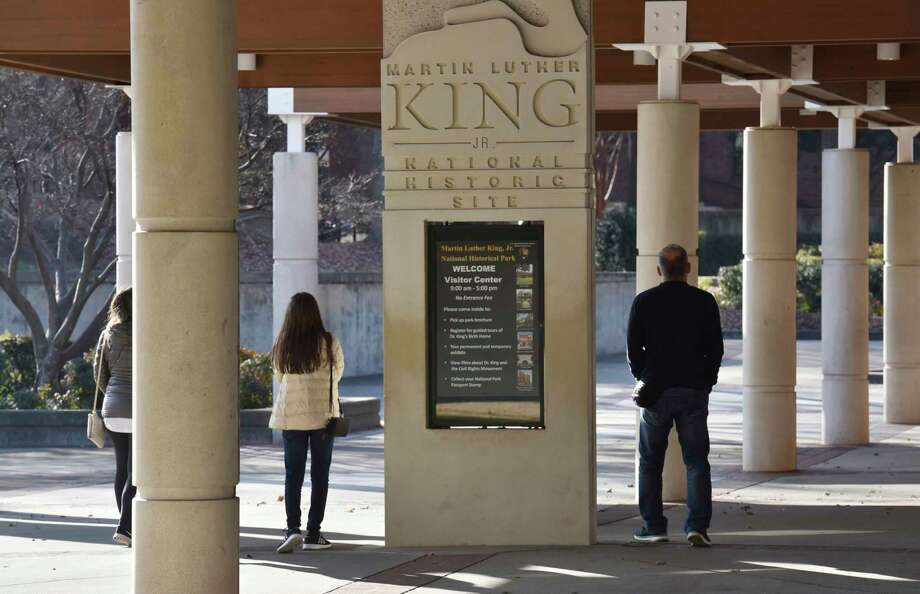 FILE - In this Dec. 22, 2018 file photo, visitors walk around the Martin Luther King, Jr. National Historical Park in Atlanta. The national landmark honoring slain civil rights leader is closed due to the partial government shutdown, but will reopen in time for the King holiday with some corporate help. Delta Air Lines announced Friday, Jan. 18, 2019  that the Martin Luther King Jr. National Historical Park in Atlanta will reopen Saturday, in time for Monday's Martin Luther King Jr. Day.   (Hyosub Shin/Atlanta Journal-Constitution via AP, File) Photo: Hyosub Shin / 2018 Atlanta Journal-Constitution