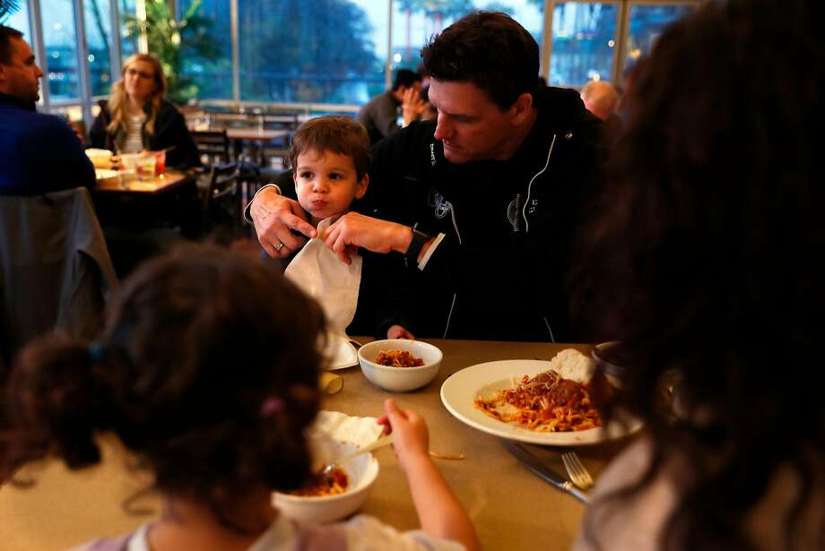 Coast Guard member James Weigand puts a napkin on his son, Parker, 2, as his wife, Krysia, and daughter, Sienna, 4, enjoy a spaghetti dinner courtesy of the South Beach Yacht Club. Photo: Photos By Scott Strazzante / The Chronicle