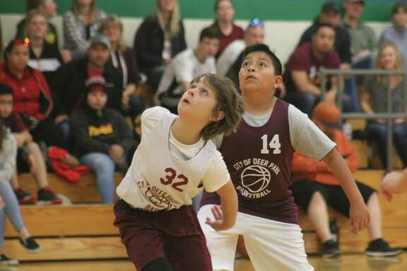 Warriors player Andy Warrick (32) watches the outcome of a free-throw attempt by a teammate during Saturday's season openers for the 10U division at Fairmont Junior High. Offensively, Warrick had a big hand in helping the team score 25 points.