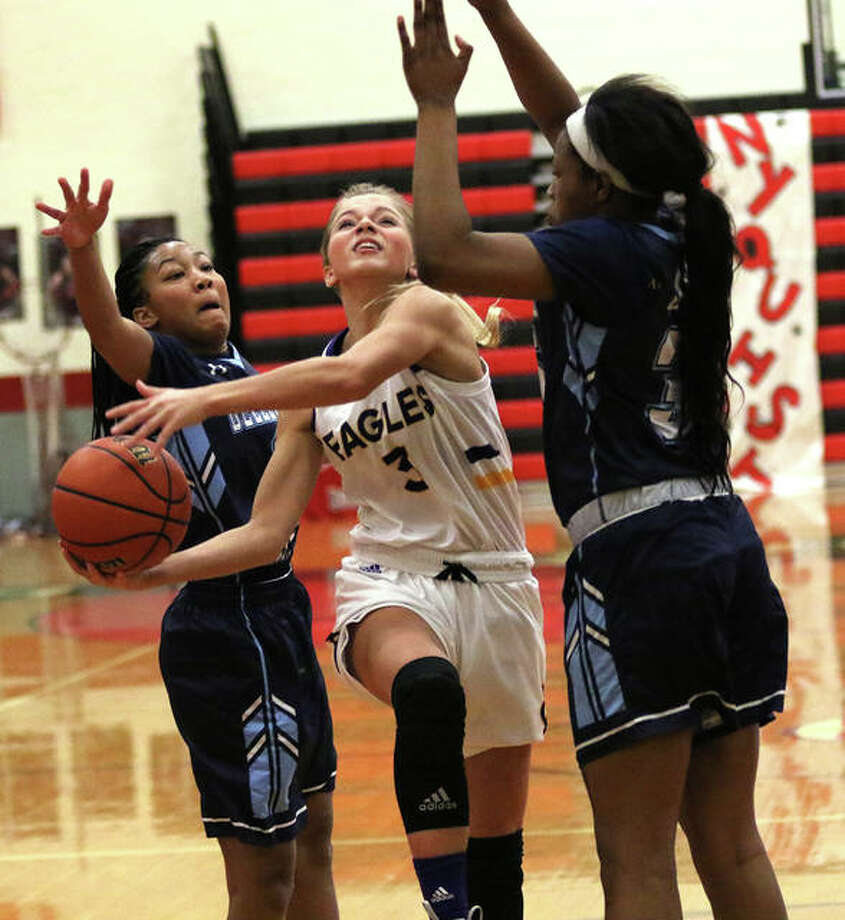 CM's Kelbie Zupan (middle) splits Belleville East's Kaylah Rainey (left) and B'Aunce Carter to put up a shot in the lane in the first half Sunday night in the championship game of the Highland Tournament. Photo: Greg Shashack / The Telegraph