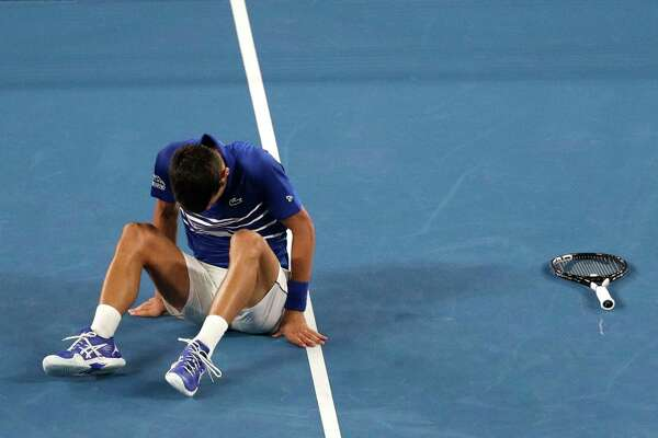 Serbia's Novak Djokovic gets back to his feet after fall during his fourth round match against Russia's Daniil Medvedev at the Australian Open tennis championships in Melbourne, Australia, Monday, Jan. 21, 2019.