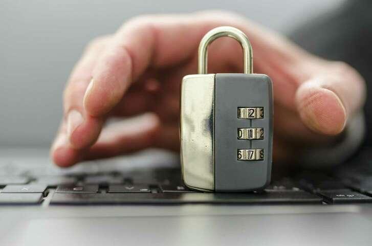 Male hand stealing padlock off computer keyboard.