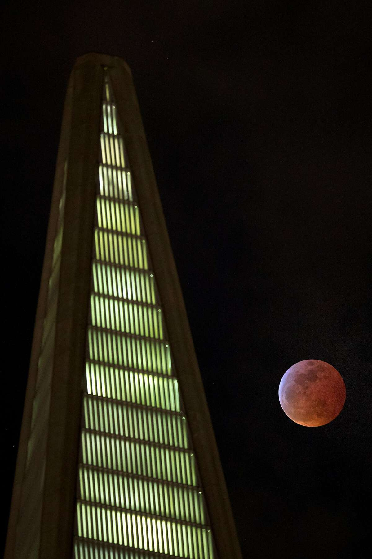 The fully-eclipsed Super Blood Wolf Moon is visible alongside the Transamerica Pyramid in San Francisco, Calif., on Sunday, January 20, 2019.