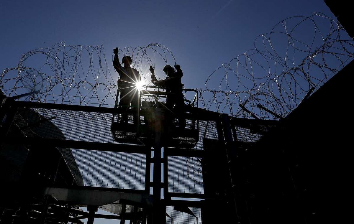 Marines from Camp Pendleton install razor wire at the pedestrian border crossing into Mexico in San Ysidro on Friday, Nov. 16, 2018. The Pentagon has agreed to keep troops deployed on the border until the end of September.