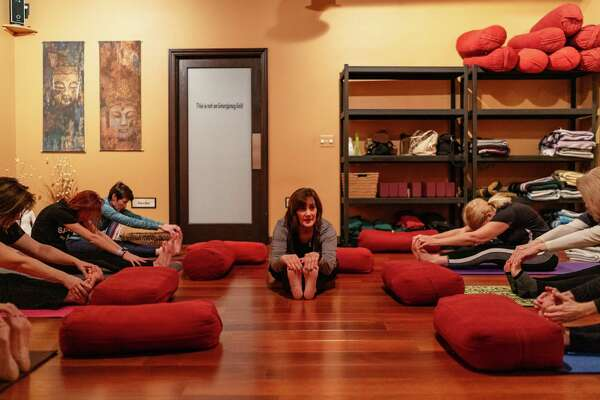 Jasmin Cromwell, center, teaches a yoga class at Bodhi Seed Yoga & Wellness Studio in Macomb County, Mich. Cromwell offers a free yoga class on Thursday mornings to government employees affected by the shutdown.