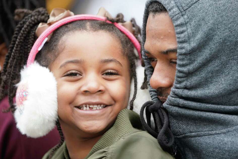 India Everhart, 5, left, and her dad, Anthony Everhart, right, try to keep warm as they wait to watch the Black Heritage Society's 41st Annual Original MLK, Jr. Day Parade Monday, January 21, 2019 in Houston.