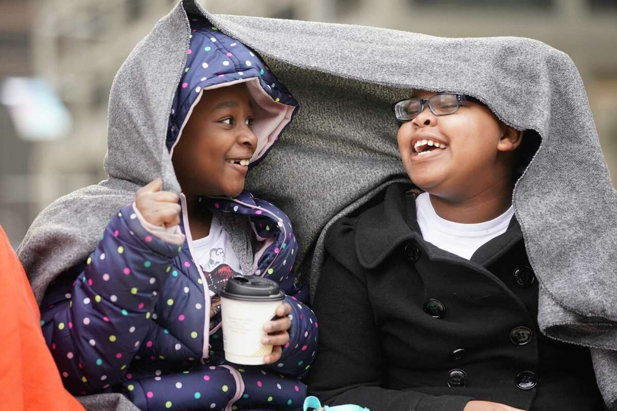 Simone Shannon, 7, left and her friend, Sydney Watson , 8, right, try to keep warm as they wait for the start of the Black Heritage Society's 41st Annual Original MLK, Jr. Day Parade Monday, January 21, 2019 in Houston.