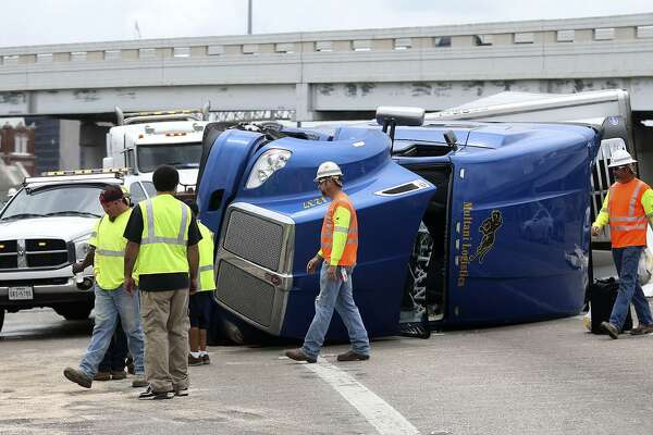 A crew works to clean up a mess Wednesday May 31, 2017 on the highway interchange connecting IH-35 southbound to IH10 westbound. The truck was carrying bottled orange juice and fruit punch and tipped over while the truck's driver tried to negotiate a turn. The driver, Vakram Singh, was not injured. Traffic traveling from IH-35 south to IH-10 west was detoured.