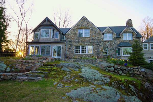 The stone and wood shingle house at 65 Cavalry Road sits on a rocky knoll on a private, yet not isolated estate called High Rock in Weston on the Westport line. Look close ... there is a rainbow above the house.