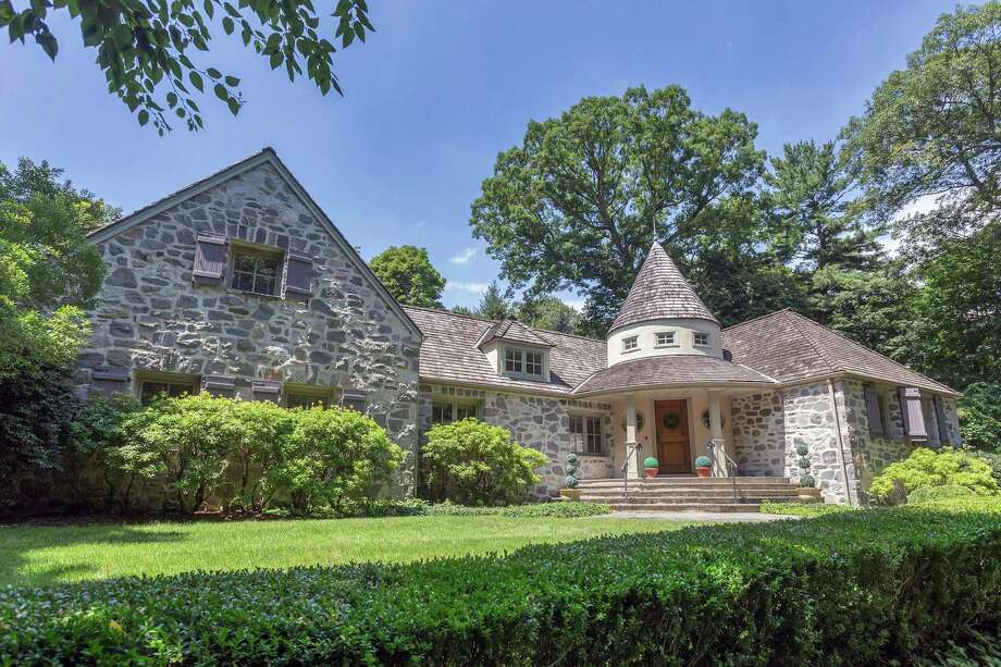 The enchanting 3,560-square-foot stone and stucco colonial house at 72 Delafield Island Road was built by the renowned architect Frazier Forman Peters in the private Delafield Island Association.