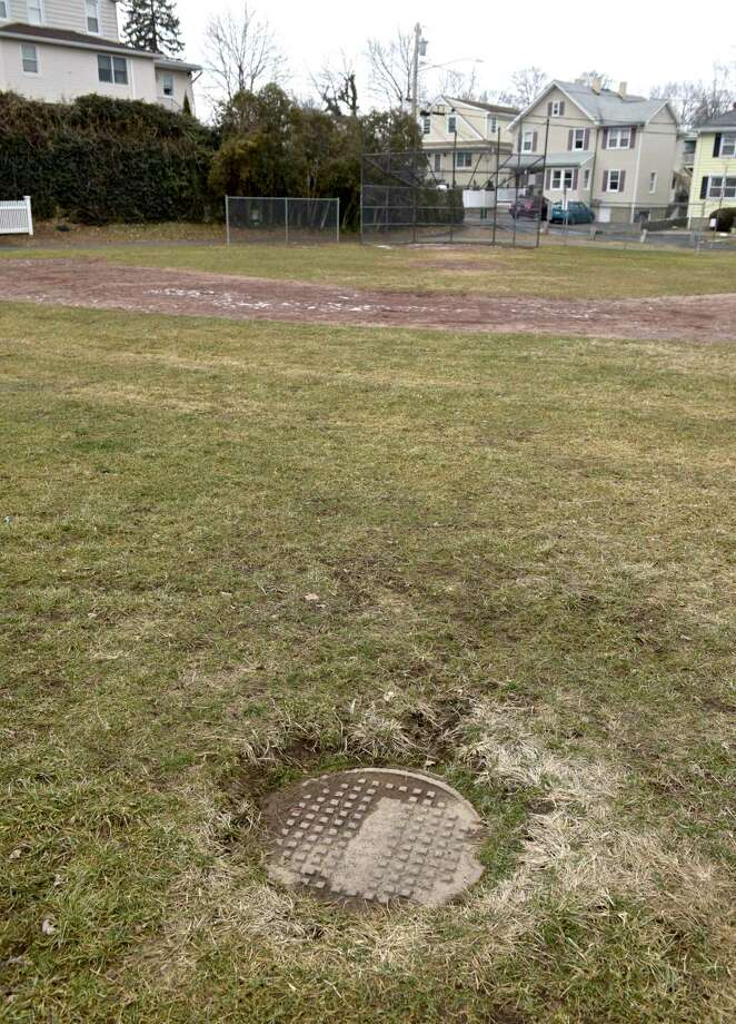 A manhole cover is behind second base at the Hamilton Avenue School field. Neighbors would like to see improvements to the schools field, they feel it is in poor condition. Friday, January 19, 2019, in Greenwich, Conn. Photo: H John Voorhees III / Hearst Connecticut Media / The News-Times