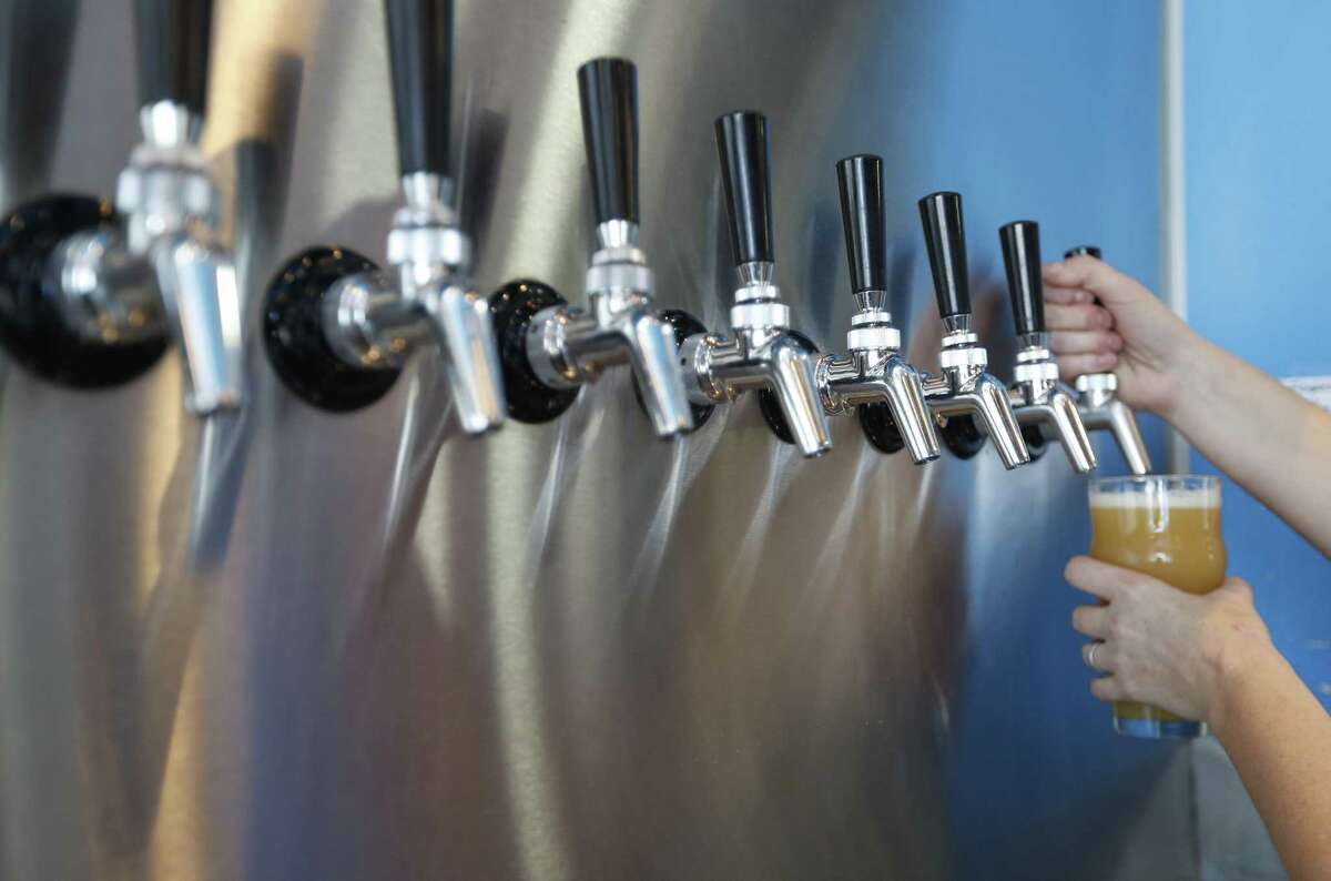 """Platypus head brewer Kerry Embertson pours a pint of """"Won't You Be My Neighbor"""" at Holler Brewing."""