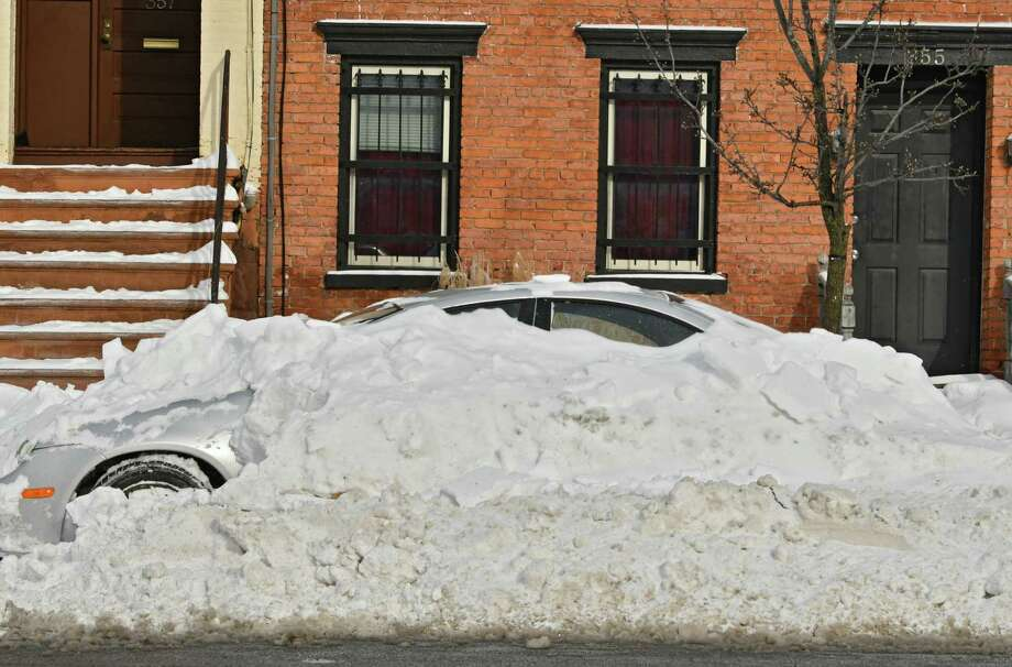 A car is mostly buried under snow the day after a snowstorm on Monday, Jan. 21, 2019 in Albany, N.Y. A snow emergency has been declared for Albany.  Beginning at 8 p.m. Monday, all vehicles must be parked on the even numbered side of the street for 24 hours. Beginning at 8 p.m. Tuesday, all vehicles must be parked on the odd numbered side of the street for the following 24-hour period. (Lori Van Buren/Times Union) Photo: Lori Van Buren, Albany Times Union / 40045986A