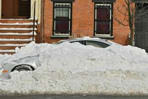 A car is mostly buried under snow the day after a snowstorm on Monday, Jan. 21, 2019 in Albany, N.Y. A snow emergency has been declared for Albany.  Beginning at 8 p.m. Monday, all vehicles must be parked on the even numbered side of the street for 24 hours. Beginning at 8 p.m. Tuesday, all vehicles must be parked on the odd numbered side of the street for the following 24-hour period. (Lori Van Buren/Times Union)