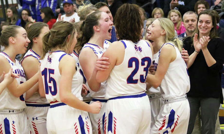 Carlinville assistant coach Renee Young (far right) watches the Cavaliers' Sarah DeNeve (middle) and Rachel Olroyd (right) celebrate with Addi Paul (far left), Gracie Reels (15), Paityn Tieman (23) and other teammates after Olroyd and Tieman brought the Macoupin County Tournament championship trophy to the team following Carlinville's 52-47 victory over the Staunton Bulldogs on Friday night in Mount Olive. The county championship was the Cavs' first since 2015 and pushed their record to 18-2 heading into Thursday's SCC home date with Gillespie. Photo: Greg Shashack / The Telegraph