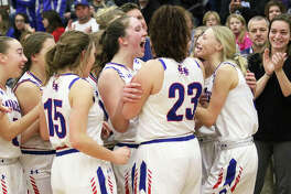 Carlinville assistant coach Renee Young (far right) watches the Cavaliers' Sarah DeNeve (middle) and Rachel Olroyd (right) celebrate with Addi Paul (far left), Gracie Reels (15), Paityn Tieman (23) and other teammates after Olroyd and Tieman brought the Macoupin County Tournament championship trophy to the team following Carlinville's 52-47 victory over the Staunton Bulldogs on Friday night in Mount Olive. The county championship was the Cavs' first since 2015 and pushed their record to 18-2 heading into Thursday's SCC home date with Gillespie.