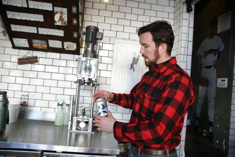 Jim Woods, founder Woods Beer and owner Cerveceria, prepares to seal a  crowler at Cerveceria on Thursday, January 7, 2015 in San Francisco, Calif.  Woods used to use glass bottles but during the Dolores Park renovation,  started looking at ways to be a good neighbor so has since switched to crowlers, a 32 oz. can which comes empty but can be filled with a customers choice.
