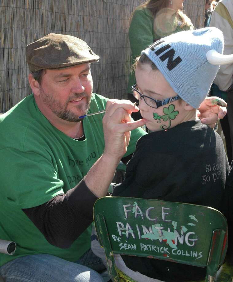 Sean Collins paints a boy's face at the Rory Miggins Irish Stew Cook-off and Music Festival. Photo: Wong, George, George Wong / Freelance
