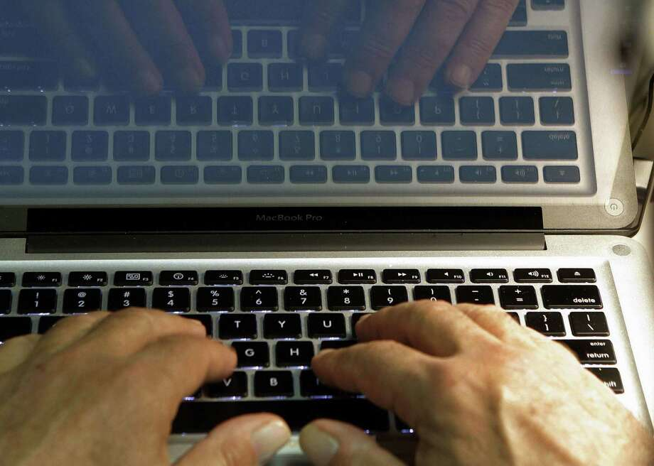 FILE - In this Feb. 27, 2013, file photo, hands type on a computer keyboard in Los Angeles. News that Facebook founder Mark Zuckerberg's rarely used Twitter, LinkedIn and Pinterest accounts were briefly compromised should serve as a reminder that we're all susceptible to hacking. (AP Photo/Damian Dovarganes, File) Photo: File Photo / Internal