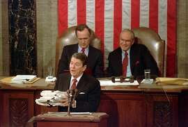 FILE - This Jan. 25, 1988 file photo shows President Ronald Reagan holding up 14-pound continuing resolution for the budget, part of a total package weighing 43-pounds, which the president said was two months late from Congress, during his State of the Union address on Capitol Hill in Washington.  Vice President George H.W. Bush, left, and House Speaker James Wright of Texas listen behind him.  (AP Photo/Bob Daugherty, File)