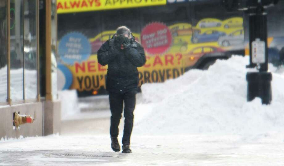 A man covers his face against the cold wind as he makes his way along North Pearl Street on Monday, Jan. 21, 2019, in Albany, N.Y.  (Paul Buckowski/Times Union) Photo: Paul Buckowski, Albany Times Union / (Paul Buckowski/Times Union)