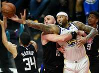 Golden State Warriors center DeMarcus Cousins, right, battles for the rebound with Los Angeles Clippers center Marcin Gortat, center, and forward Tobias Harris (34) during the third quarter on Friday, Jan. 18, 2019 in Los Angeles, Calif.