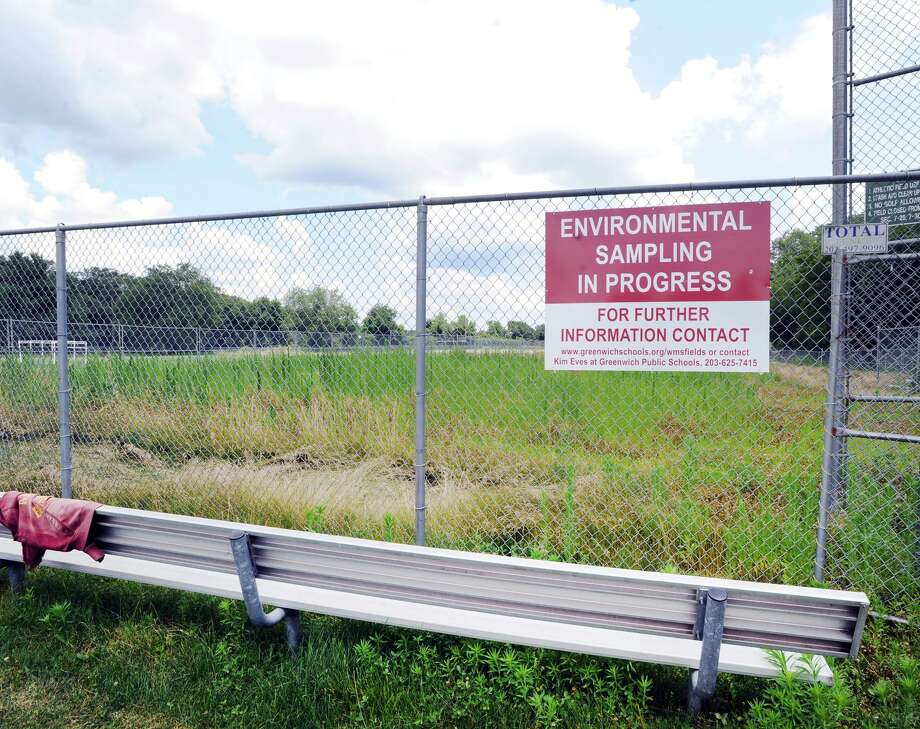 """Environmental Sampling In Progress,"" reads the sign at the ball field at Western Middle School in Greenwich, Conn. Wednesday, July 11, 2018. Part of Western's fields reopened for student use in September 2017, but a large portion, including the one shown here has remained closed and fenced off since August 2016, when high levels of PCBs, arsenic, lead and chlordane were found in the soil. Photo: File. / Hearst Connecticut Media / Greenwich Time"