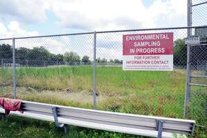 """""""Environmental Sampling In Progress,"""" reads the sign at the ball field at Western Middle School in Greenwich, Conn. Wednesday, July 11, 2018. Part of Western's fields reopened for student use in September 2017, but a large portion, including the one shown here has remained closed and fenced off since August 2016, when high levels of PCBs, arsenic, lead and chlordane were found in the soil."""