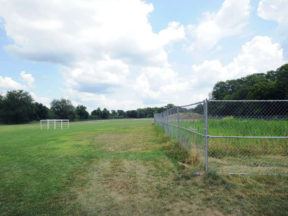 The athletic fields, open at left, closed at right due to toxicity issues with chemicals in the soil, at Western Middle School in Greenwich, Conn. Wednesday, July 11, 2018. Part of Western's fields reopened for student use in September 2017, but a large portion, including the softball field has remained closed and fenced off since August 2016, when high levels of PCBs, arsenic, lead and chlordane were found in the soil. Photo: File / Hearst Connecticut Media / Greenwich Time